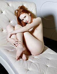Redhead Bella Milano shows off sweet, pink pussy on the couch.