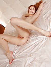 Redhead Adel C flaunts her smoking hot body as she poses on the bed.