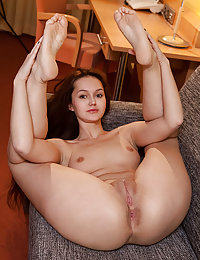 Sintia bares her delectable pussy as she sensually strips on the chair.
