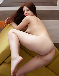 Redhead Sienna flaunts her naked, slender body as she poses on the couch.