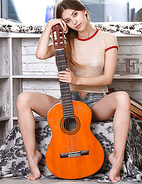 Avery displays her sexy, slender body as she poses with her guitar.