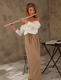 Tempe sensually poses on the chair as she plays her flute.