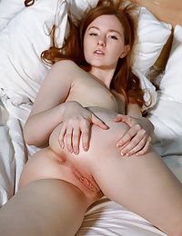 Redhead Anicka displays her creamy body and sweet pussy as she lays on the bed.